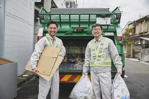 パッカー車とゴミを持つ男性の作業員の写真素材 [FYI04796480]