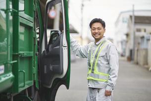 パッカー車と笑っている男性の作業員の写真素材 [FYI04796481]