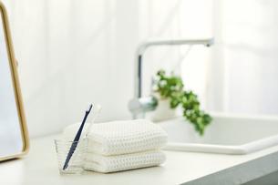 洗面所に置かれたタオルと鏡と歯ブラシの写真素材 [FYI04796750]