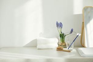 洗面所に置かれたタオルと鏡と歯ブラシとヘアブラシの写真素材 [FYI04796797]