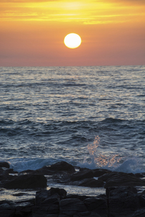 水平線に沈む夕陽と岩の海岸の写真素材 [FYI04797737]