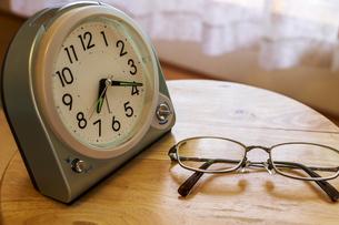 机の上に置かれた置き時計と眼鏡の写真素材 [FYI04798193]