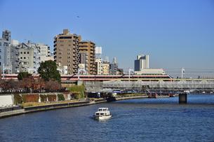隅田川橋梁を走る東武伊勢崎線と隅田川を渡る船舶とビル群の写真素材 [FYI04798990]