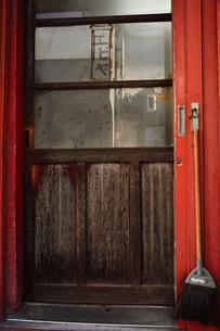 浅草仲見世の赤い木製外壁の裏口にかけられた箒の写真素材 [FYI04799001]