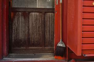 浅草仲見世の赤い木製外壁の裏口にかけられた箒の写真素材 [FYI04799002]