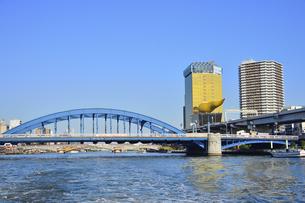 水上バスから見た駒形橋と1989年にアサヒビール創業100周年を記念にスーパードライホール屋上に建設された「フラムドール」(フランス語で金の炎)と呼ばれるオブジェとビル群の写真素材 [FYI04799020]