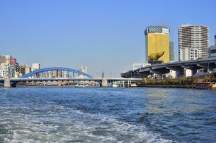 水上バスから見た駒形橋と1989年にアサヒビール創業100周年を記念にスーパードライホール屋上に建設された「フラムドール」(フランス語で金の炎)と呼ばれるオブジェとビル群の写真素材 [FYI04799022]