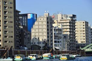 水上バスから見た隅田川に停泊している数隻の船とビル群の写真素材 [FYI04799026]