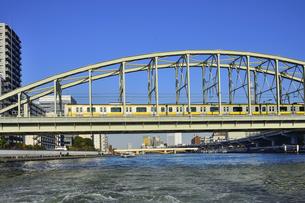 水上バスから見たJR総武線電車が走る隅田川橋梁と蔵前橋と水上バスとビル群の写真素材 [FYI04799032]