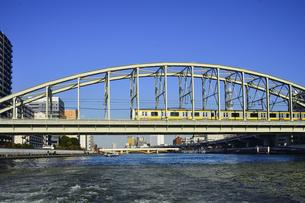 水上バスから見たJR総武線電車が走る隅田川橋梁と蔵前橋と水上バスとビル群の写真素材 [FYI04799033]