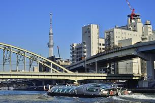 水上バスから見たJR総武線の隅田川橋梁と隅田川を渡る水上バスとスカイツリーとビル群の写真素材 [FYI04799034]