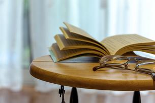 テーブルの上に置かれた本と眼鏡の写真素材 [FYI04799840]