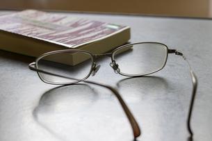 机の上の本と眼鏡の写真素材 [FYI04799850]