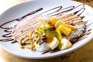 生クリームとチョコソースとフルーツとナッツのパンケーキの写真素材 [FYI04800352]