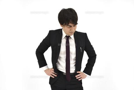 悩んでいるスーツの男性 白背景の写真素材 [FYI04800497]