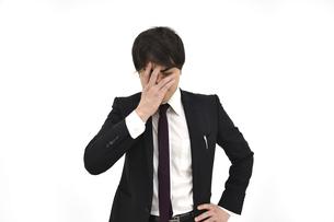 悩んでいるスーツの男性2 白背景の写真素材 [FYI04800498]