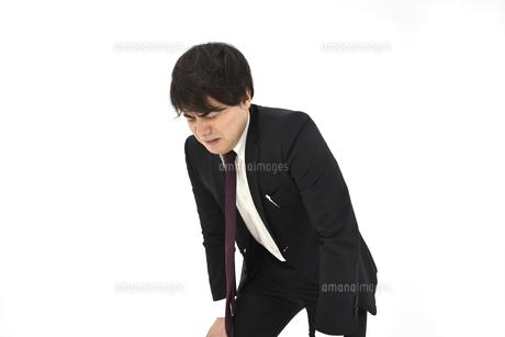 苦しんでいるスーツの男性 白背景の写真素材 [FYI04800499]