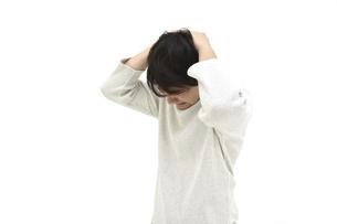 頭を抱えて悩んでいるカジュアルの男性 白背景の写真素材 [FYI04800520]