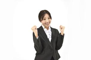 ガッツポーズで成功を喜んでいるスーツの女性 白背景の写真素材 [FYI04800749]