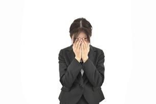 悲しんで顔を覆っているスーツの女性 白背景の写真素材 [FYI04800753]