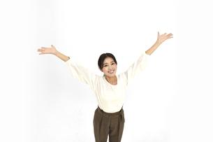 空を仰いで両手を広げるカジュアル女性2 白背景の写真素材 [FYI04800921]