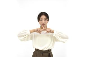 両指でバツをするカジュアル女性 白背景の写真素材 [FYI04800924]