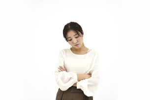 両腕を組み悩むカジュアル女性1 白背景の写真素材 [FYI04800926]