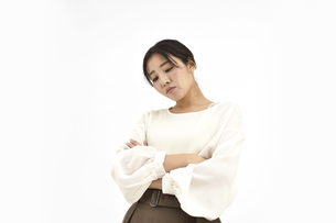 両腕を組み悩むカジュアル女性2 白背景の写真素材 [FYI04800927]