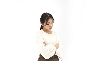 両腕を組み悩むカジュアル女性3 白背景の写真素材 [FYI04800928]
