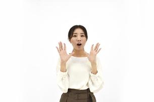 両手を広げて驚くカジュアル女性1 白背景の写真素材 [FYI04800929]