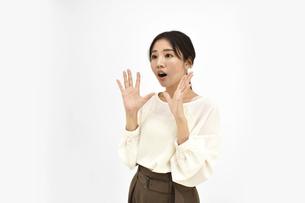 両手を広げて驚くカジュアル女性2 白背景の写真素材 [FYI04800930]
