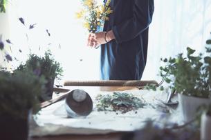 黄色の花のミモザを持つ女性の写真素材 [FYI04801112]