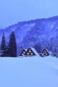 雪の白川郷 合掌造り集落の窓明かり夕景の写真素材 [FYI04801469]