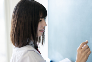 黒板に向かう女子学生の横顔の写真素材 [FYI04801745]