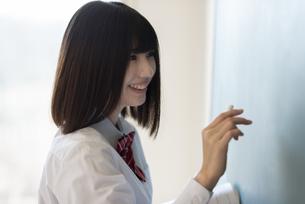 黒板に向かう女子学生の横顔の写真素材 [FYI04801746]