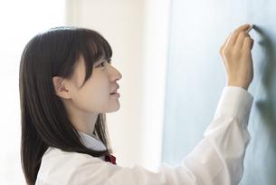 黒板に向かう女子学生の横顔の写真素材 [FYI04801750]