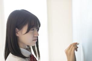黒板に向かう女子学生の横顔の写真素材 [FYI04801751]