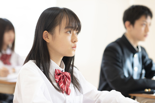 教室で授業を受ける女子学生の横顔の写真素材 [FYI04801758]