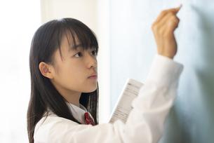 黒板に向かう女子学生の横顔の写真素材 [FYI04801762]