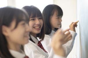 黒板の前に立つ女子学生の写真素材 [FYI04801766]