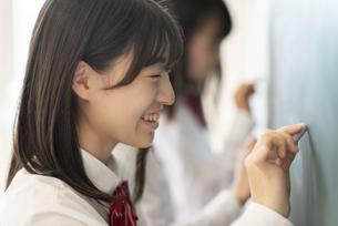 黒板の前に立つ女子学生の写真素材 [FYI04801767]
