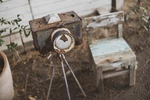 アンティーク・レトロなカメラのオブジェと小さい木の椅子の写真素材 [FYI04802151]