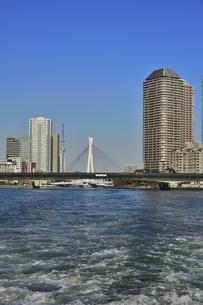 水上バスから見た中央大橋(奥)と佃大橋と東京スカイツリーとビル群と空と波の写真素材 [FYI04802171]