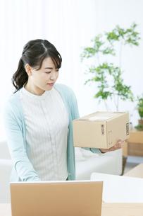 荷物を持ちながらパソコンを操作する女性の写真素材 [FYI04803760]