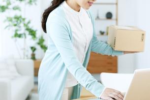 荷物を持ちながらパソコンを操作する女性の写真素材 [FYI04803762]