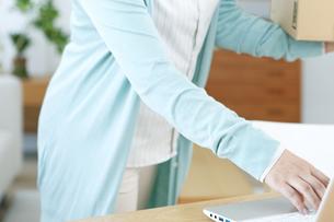 荷物を持ちながらパソコンを操作する女性の手元の写真素材 [FYI04803763]