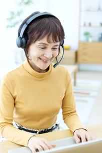 インカムを付けてパソコン操作するシニア女性の写真素材 [FYI04803784]