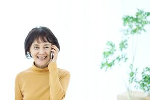 スマートフォンで通話するシニア女性の写真素材 [FYI04803800]