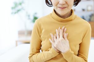 胸元に両手をあてるシニア女性の写真素材 [FYI04803807]