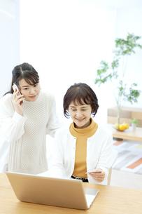 スマートフォンで通話する娘とネットショッピングする母の写真素材 [FYI04803843]